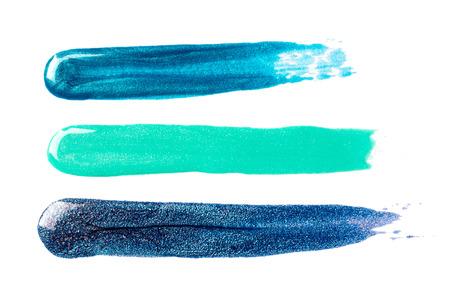 Sparkling blue nail polish strokes isolated on white. Stock Photo