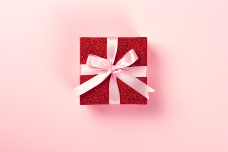 Red gift box with pink ribbon on pink background. Christmas, Valentines day or birthday concept. Place for text. Stock Photo