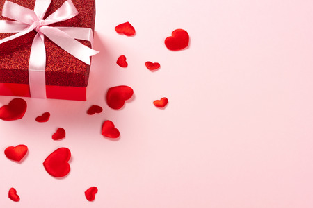 Red gift box with pink ribbon and scattered red hearts on pink background. Christmas, Valentines day or birthday concept. Place for text. Stock Photo