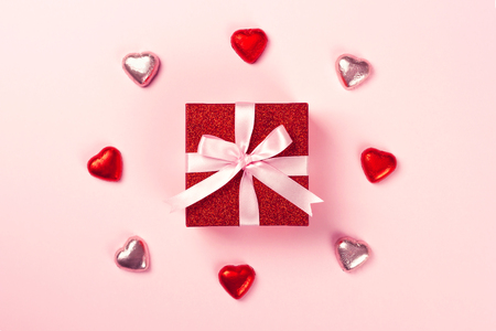 Red gift box with pink ribbon and chocolate heart shaped candies on pink background. Christmas, Valentines day or birthday concept.