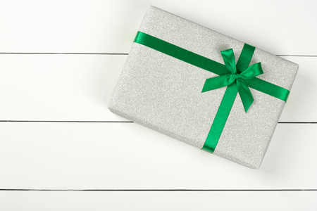 Light gray glitter gift box with satin green ribbon on white wooden background. Christmas, holidays and celebration concept. Flat lay style. Copy space for text.