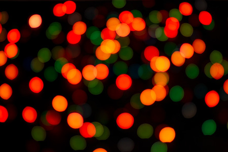 Abstract multicolor bokeh texture on black background. Defocused sparkles.