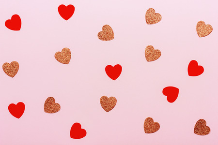 Minimal Valentines day background. Heart shaped confetti on pink pastel background. Holiday decoration concept.