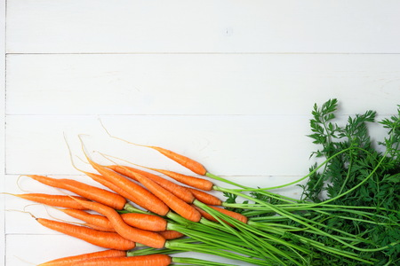 Bunch of whole fresh raw carrots on white wooden background. Copy space for your text.