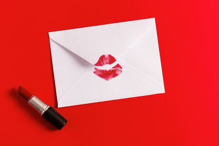 Red lipstick kiss on white envelope on red background. Love letter concept. Valentines day.