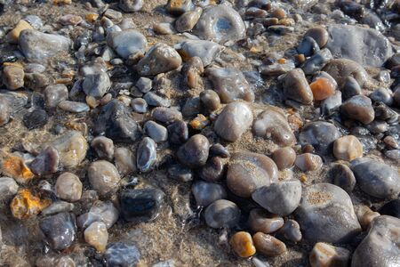 Colorful pebble stones under sea water. Beach scene. Textured background.