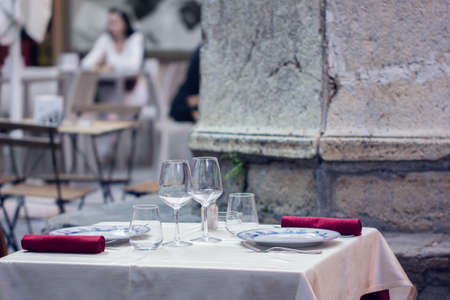 Empty outdoor restaurant table for two. Summer terrace cafe. Blurred background.