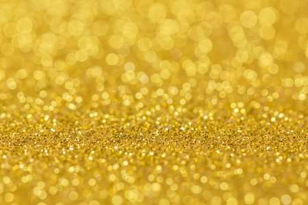 Abstract gold background with bokeh effect. Blurred glitter.