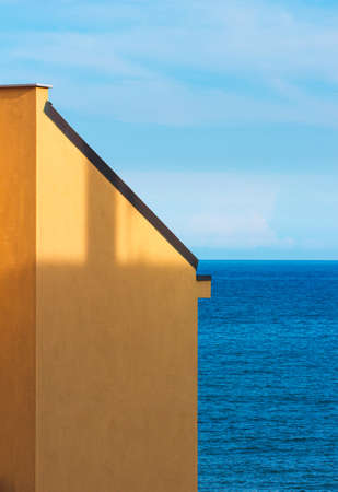Yellow wall of building with a sea and sky background. Minimal abstract concept. Reklamní fotografie
