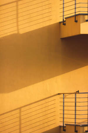 Yellow wall with balconies with shadows. Minimal abstract concept.