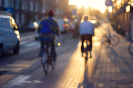 Blurred street view with two men on bicycles in sunset light. Abstract background of city view.