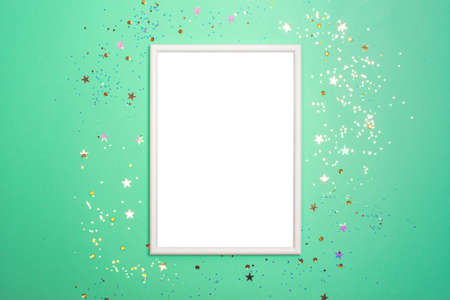 Festive background with blank white photo frame on light green with scattered confetti. Mock up for photo or text. Top view. Flat lay style.