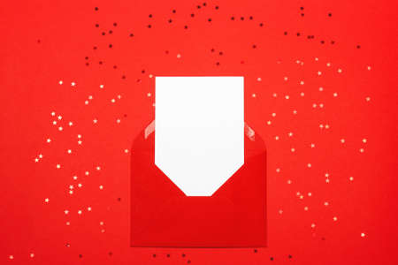 Greeting card for Valentines day. Red envelope with empty white card on red background. View from above. Holiday or correspondence concept. Place for text.