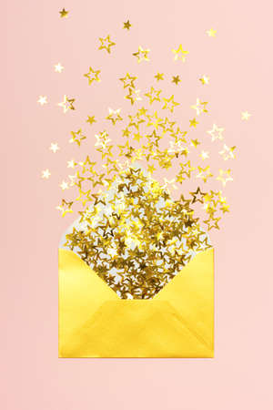 Golden star shaped confetti pouring out of golden envelope on pink background. Correspondence concept.