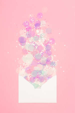 Sparkling confetti pouring out of white envelope on pastel pink background. Correspondence concept.