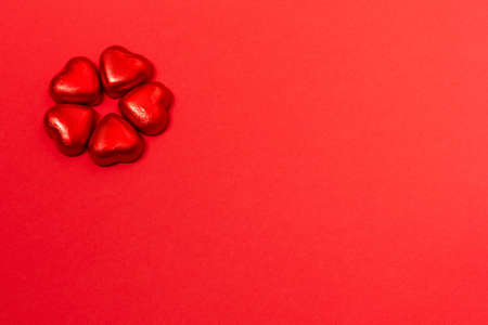 Chocolate heart shaped wrapped candies on red paper background. Minimal Valentines day background. Copy space for your text.