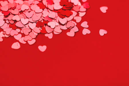 Beautiful festive background with red metallic heart shaped confetti. Valentines day background. Copy space for your text. Selective focus.