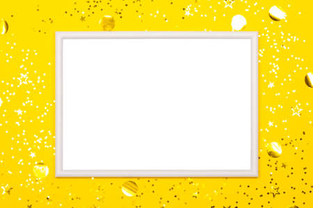 Festive background with blank white photo frame on yellow with scattered confetti. Mock up for photo or text. Top view. Flat lay style.