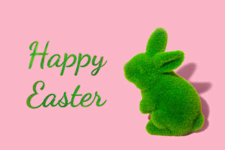 Easter green grass bunny on pink background. Minimal greeting card concept with text. Фото со стока