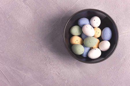 Candy Easter eggs in a dark ceramic bowl on gray concrete background. Top view, copy space for text. Holiday decoration concept. Фото со стока