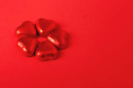 Heart shaped wrapped chocolate candies on red paper background. Minimal Valentines day background. Copy space for your text. Фото со стока