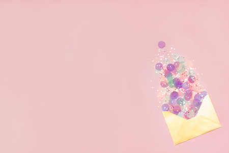 Sparkling confetti pouring out of golden envelope on pastel pink background. Correspondence concept. Flat lay. Place for text.