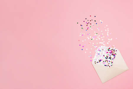 Sparkling confetti pouring out of envelope on pastel pink background. Correspondence concept. Flat lay. Place for text.