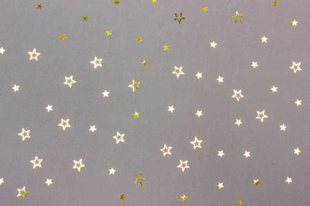 Festive gray background with scattered star shaped golden confetti. Top view. Flat lay style. Color trend 2021. Фото со стока
