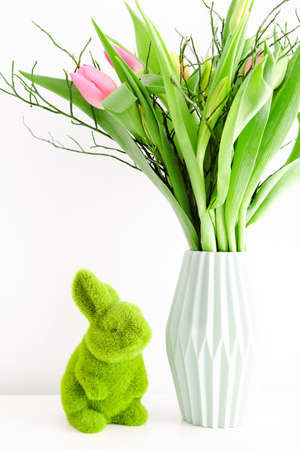 Bouquet of multicolored unopened tulips in light green ceramic vase and Easter green grass bunny on white wall background. Holiday decoration concept. Фото со стока