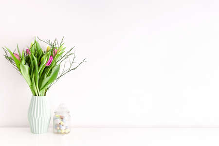 Bouquet of multicolored unopened tulips in light green ceramic vase and Easter candy jar filled with eggs on white wall background. Home interior decoration concept. Place for text.