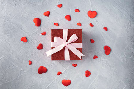 Red gift box with pink ribbon and scattered red hearts on gray background. Valentines day or birthday concept. Фото со стока