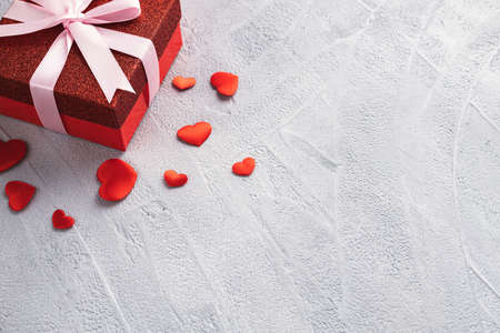 Red gift box with pink ribbon and scattered red hearts on gray background. Valentines day or birthday concept. Place for text.