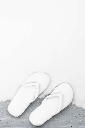 Forgotten flip flops in the snow. Unexpected weather concept. Фото со стока