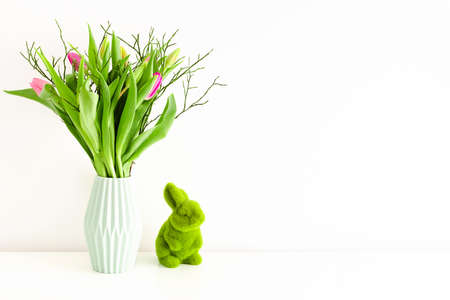 Bouquet of multicolored unopened tulips in light green ceramic vase and Easter green grass bunny on white wall background. Holiday decoration concept. Place for text.