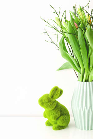 Bouquet of multicolored unopened tulips in light green ceramic vase and Easter green grass bunny on white background. Holiday decoration concept.