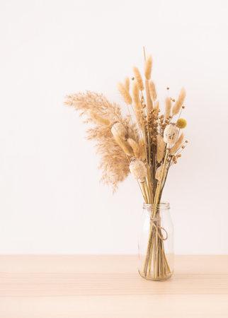 Bouquet of beige dried flowers in a glass vase on beige background.