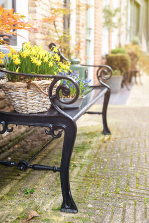 A bench next to the front door of a house with flower decoration.