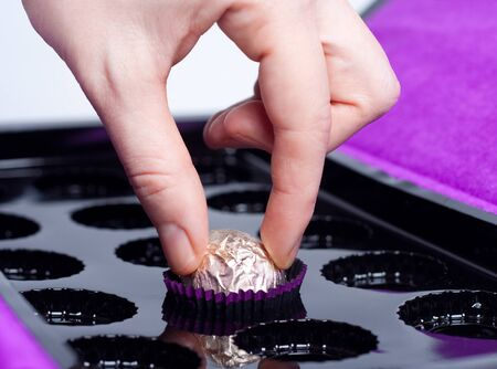 womans hand taking the last chocolate candy in the box photo