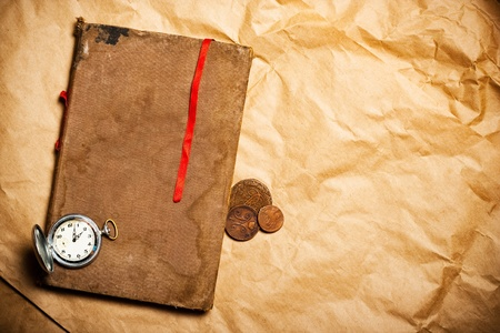red book: old book with red bookmark and antique watch and coins on yellow paper