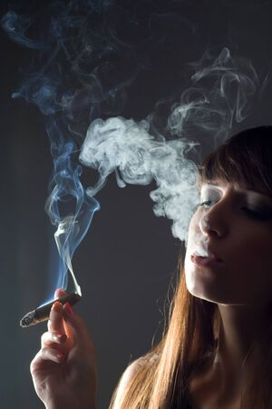 backlight image of girl smoking cigar photo