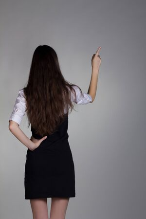 girl in black dress from behind shows something photo