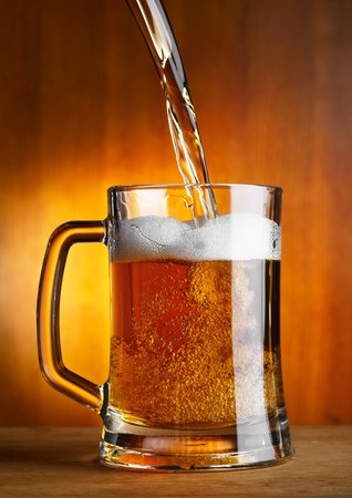 Beer is pouring into glass photo
