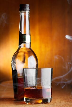 whiskey bottle: glass and bottle of whiskey with smoke Stock Photo