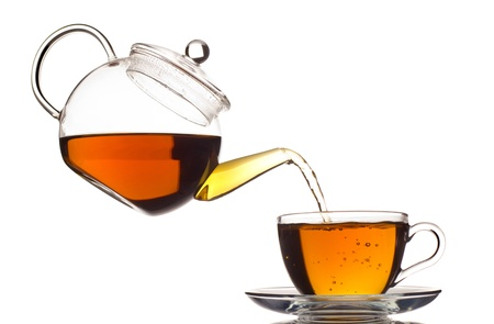 yellow tea pot: tea pouring in the cup isolated on white Stock Photo