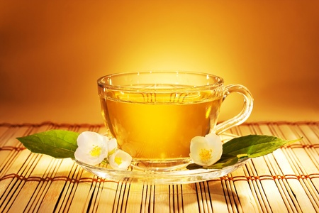 teatime: jasmine tea in soft warm evening light with fresh jasmine leaves and flowers  Stock Photo