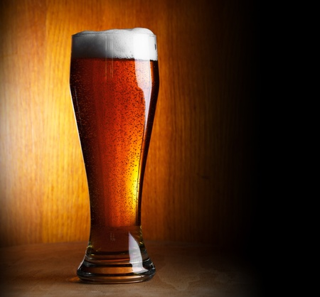 unbottled: glass of beer on dark background with copy-space
