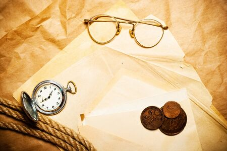antique money with watch, glasses and rope on envelope photo