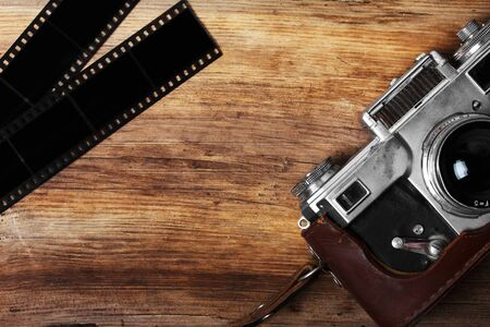 old camera: old camera and blank film strip on wooden table