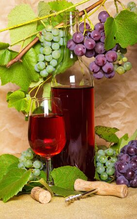 wine with red and white bunch of grapes on sacking photo
