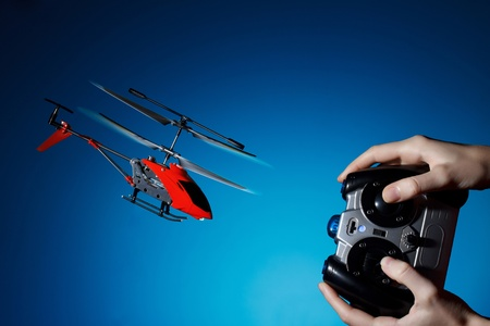 piloting: Piloting remote control helicopter Stock Photo
